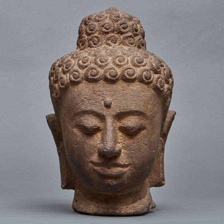 Stone head of a Buddha on a black wooden stand. Cambodia, Khmer. 20 th century. Size: Head : 32 cm; Base : H. : 59 cm. Shipping and handling not included.