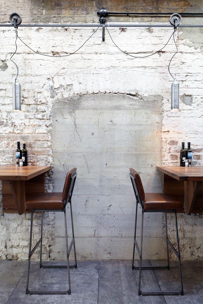 Restaurant Balthasar Köln | Michels Architekturbüro  Historisches Mauerwerk, Hängelampen an Rollen auf Schienen, schlichte Stühle