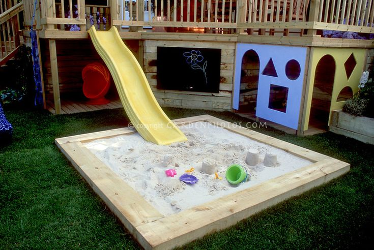 Deck with kids in mind. Design: Boardman, Gelly & Co. Sandbox, sliding board pond, home landscaping, colorful backyard playground, lawn grass, chalk board, entertaining children at home