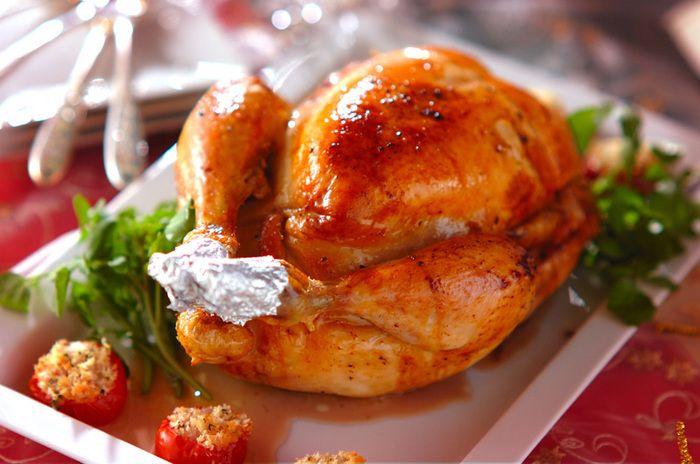 これぞクリスマス!という丸焼きのローストチキン。鶏レバーやベーコン、玉ネギ、セロリ、ニンニク、バケットなどを、みじん切りにして詰め、200℃に予熱しておいたオーブンで30分焼き、時々底にたまった油をかけながら、さらに約40分焼いて完成です。華やかな本格派ローストチキンに心も弾む♫