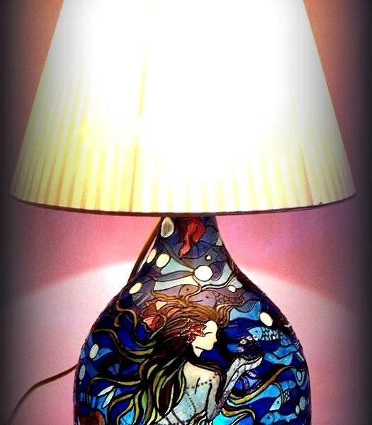 La03 Cuore d'Oceano Lampada dipinta a mano  Lampada dipinta a mano in trasparenza con doppia luce interna ( una diretta verso l'interno della base in vetro e l'altra verso il paralume). Il dipinto di Hanùl rappresenta una sirena immersa dalle onde marine che diventano pesci, quasi un tutt'uno col mare. La lampada è poi impreziosita da un delizioso paralume avorio plissettato .Effetto ottico e giochi di luce sulle pareti garantiscono una suggestione senza eguali.  Per avere informazioni su…