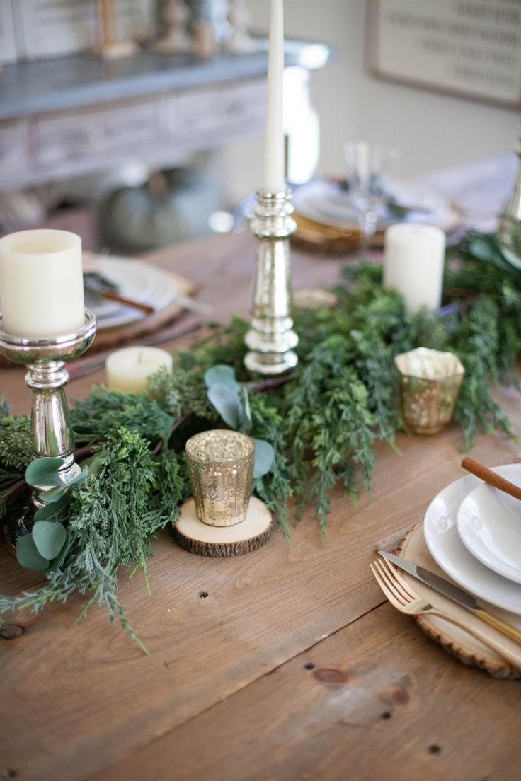A beautiful farmhouse Christmas tablescape with rustic elements, mixed metals, and natural greenery. Perfect for a hosting a holiday dinner!