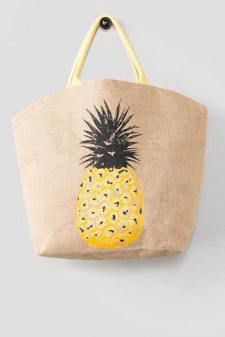 Soak up the sun in style with the Pineapple Beach Tote! This genuine jute tote features a traditional tan canvas material with a large pineapple print and yellow handles.