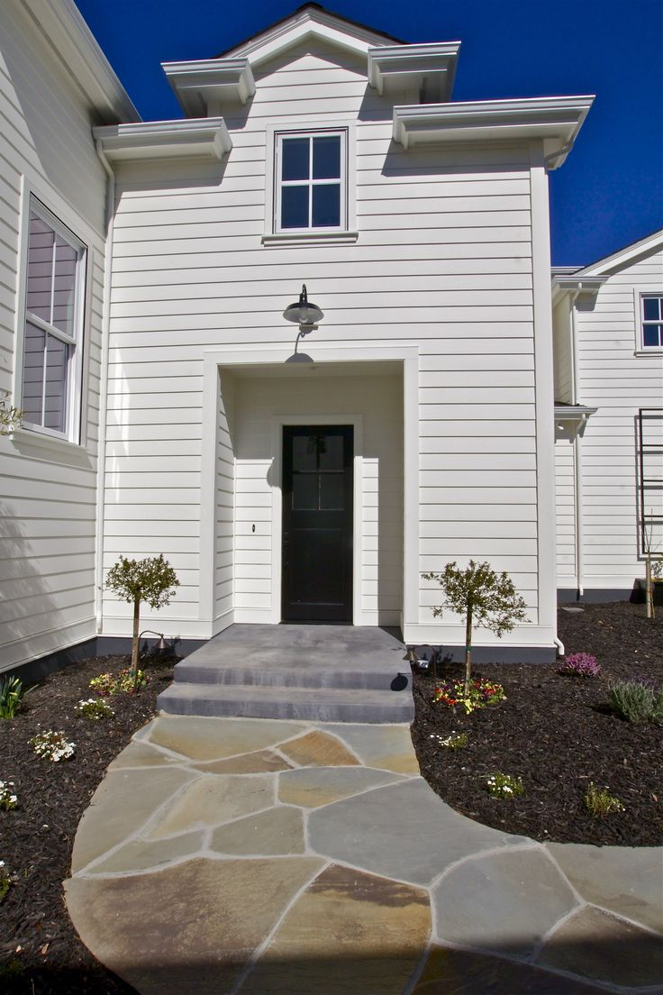 Contemporary Farmhouse entry. White house with black door and stone walkway. The color used on the house is Benjamin Moore White Chocolate - KCS, inc.