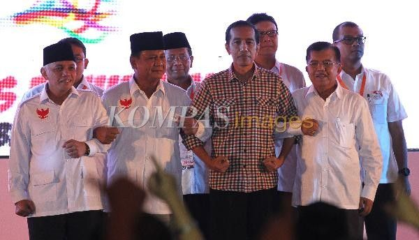 Pasangan calon presiden dan wakil presiden Prabowo Subianto-Hatta Rajasa bersama Joko Widodo-Jusuf Kalla saling berpegangan tangan usai mengikuti acara Deklarasi Pemilu Berintegritas dan Damai di Jakarta, Selasa (3/6/2014). Deklarasi yang diselenggarakan Komisi Pemilihan Umum ini menandai dimulainya masa kampanye pilpres dari 4 Juni hingga 5 Juli 2014