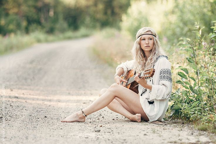 a young blond with an acoustic guitar waering bohemian clothes