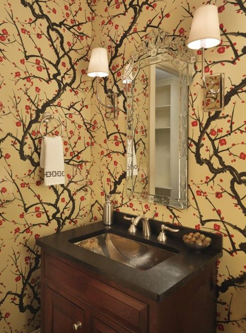 An Asian-inspired wallpaper in yellow and red gives movement and adds interest to this small powder room.
