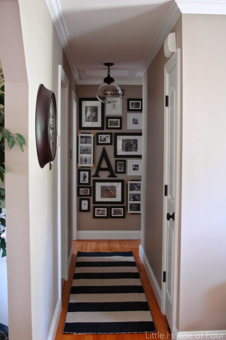 A striped rug, black and white gallery wall and updated light fixture spruce up an otherwise boring hallway.