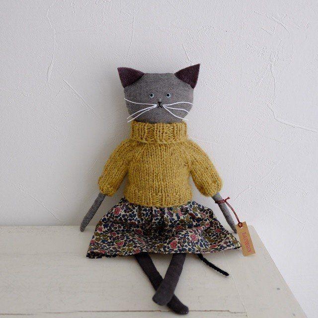 オーガニックコットンのボディに マスタードイエローの手編みのタートルセーター、Libertyファブリックのスカートを着たKitty  ひょろっとした脚はダークグリーンのリネン  瞳はペールグリーンのヴィンテージスパンコール(made in France)とグラスビーズで刺繍しました  着せ替えも可能です  小さな女の子や、大人の女性のお部屋に   Size: 高さ :約 30㎝     ※自立は出来ません。    ■素材 オーガニックコットン リネン ウール ヴィンテージスパンコール