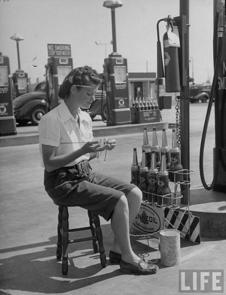 Girl knitting during slow moments at the Gilmore self-service gas station, 1948.