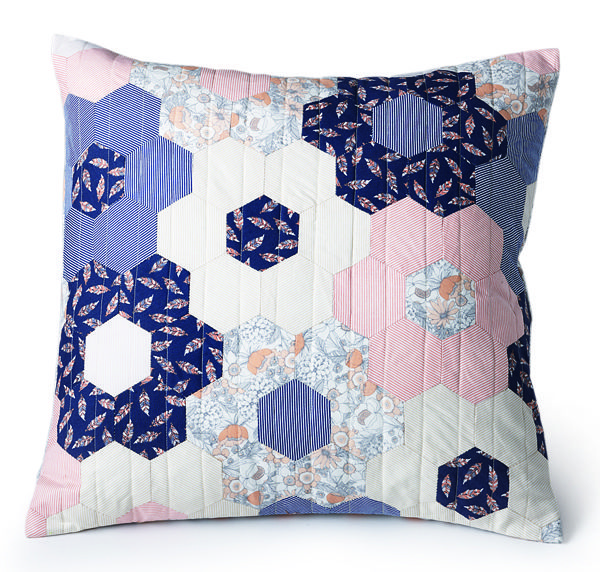 "This 20"" quilted pillow features hexagon flowers in navy, peach and cream colored patterns. Video tutorial included! #Englishpaperpiecing #MarianneFons #smallproject"