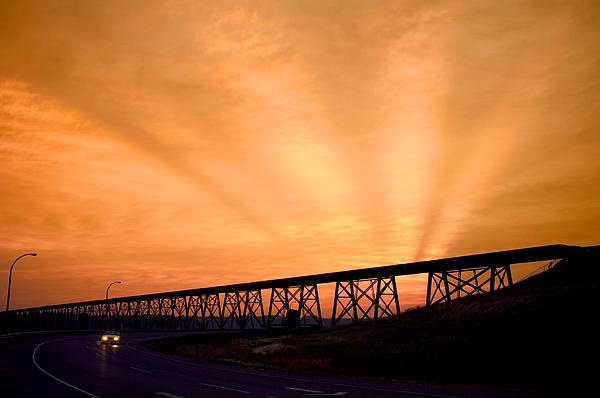And The Sky Was On Fire    The setting sun lights up the clouds above the High Level Bridge in Lethbridge, Alberta, Caada. The shadow streaks might be caused by the mountains the sun is going behind, or maybe other clouds.    Prices start at $27