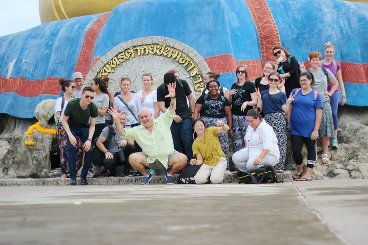 Teachers in Thailand posing at the base of a giant Buddha statue