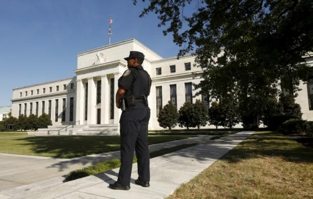 A Federal Reserve police officer keeps watch while posted outside the Federal Reserve headquarters in Washington, September 16, 2015.  REUTERS/Kevin Lamarque