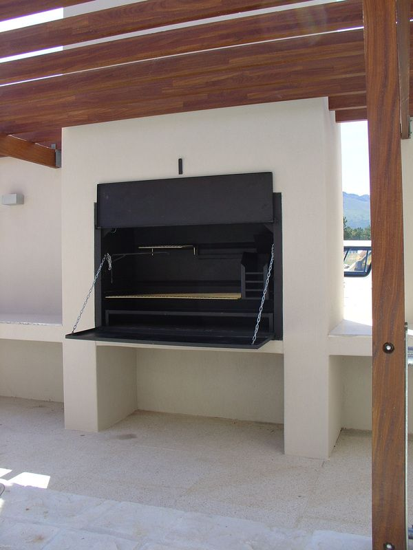 The Braai is a versatile outdoor, wood burning barbecue, come oven. It is a beautifully elegant and stylish design feature for any outdoor entertaining/ dining area and forms a social hub at parties and gatherings with family and friends.   Cooking possibilities of the Braai include grilling, slow roasting on the higher shelf, stewing in a Potjie (Dutch oven) which hangs on a high hook, smoking, pizza making and bread making.
