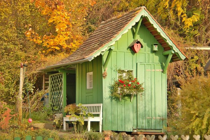 Quaint green garden shed situated amidst dense trees with a relaxing chair and floral highlights