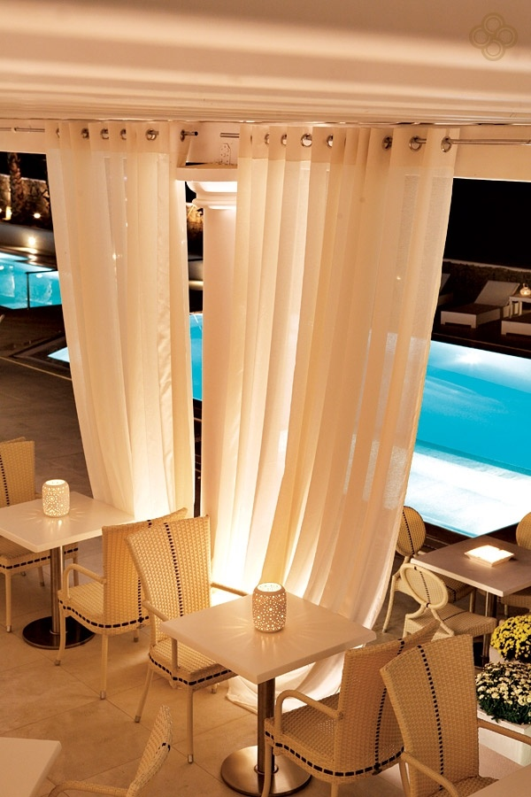 Photo the La Veranda Restaurant by night. The candles are lit and the curtains are drawn, to reveal the magnificent outdoor pools of the La Residence 5 Star Luxury Hotel Suites in Mykonos.