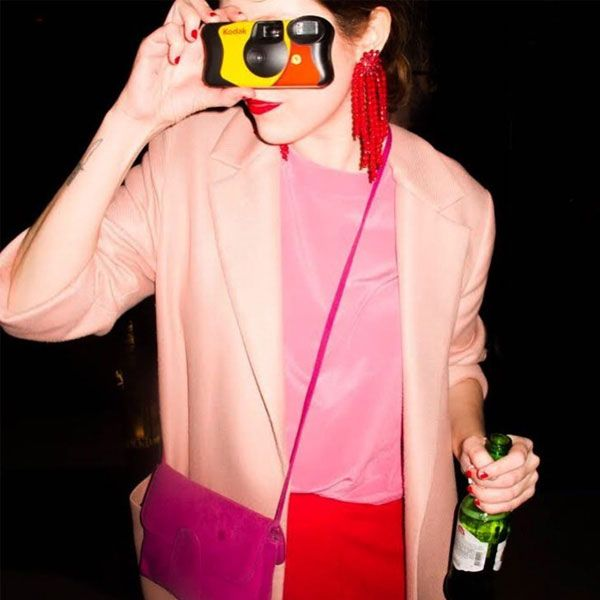 Combinação de rosa e vermelho com blazer rosa e calça vermelha, completando o look com bolsa com tom mais forte de rosa e brincos vermelhos.