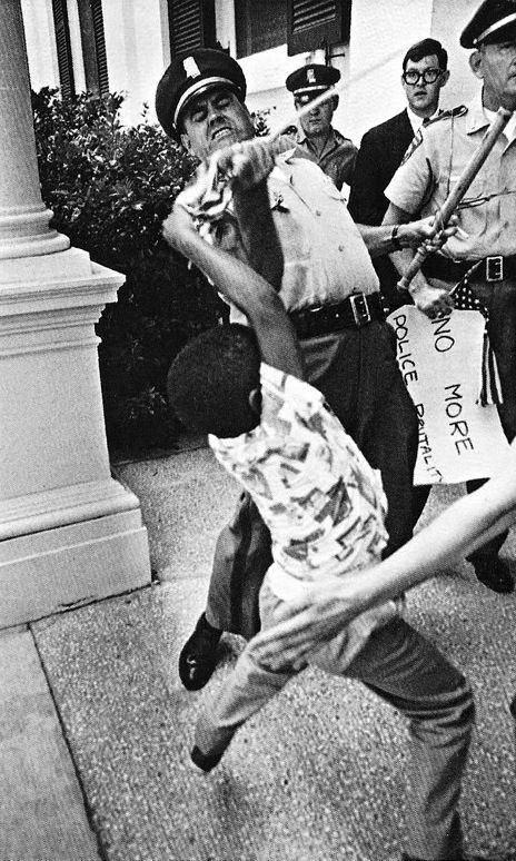 In 1965, at Jackson, Mississippi, Matt Herron took an iconic and ironic image from the civil rights era as a white policeman rips an American flag away from a young black boy, having already confiscated his 'No More Police Brutality' sign.