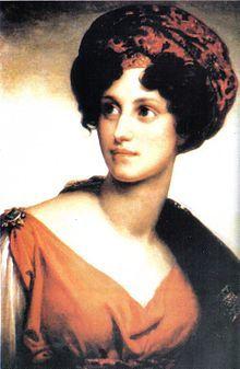 Morceau d'une peinture ou gravure en couleurs, représentant le haut du corps d'une femme, de trois-quarts et le corps légèrement tourné vers la droite, tournant la tête pour regarder en haut à gauche. Son visage est mince, ses yeux noirs, son nez droit. Elle sourit légèrement; ses cheveux noirs et bouclés sont coiffés d'une sorte de turban rouge brodé de noir, ou l'inverse. Elle porte une tunique à l'antique, décolletée, rouge et agrafée à l'épaule par une broche en étoile, et une cape…