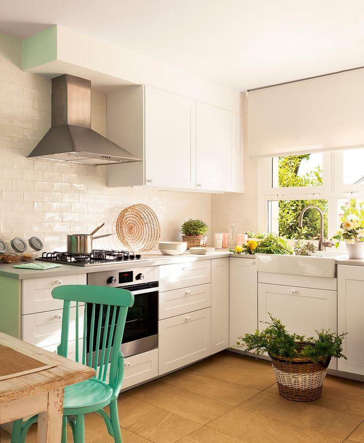 Luminosa cocina en blanco con azulejos brillantes que reflejan la luz y silla azul
