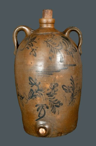 """Very Rare Morgantown, WV Stoneware Commemorative Water Cooler with Elaborate Flowering Vine Decoration, attributed to the Thompson Pottery, Morgantown, WV, circa 1875, semi-ovoid jug with tooled shoulder and spout, ribbed open handles, and circular bung hole at base, decorated on the front with two rows of flowering vines separated by cobalt brushwork. Reverse decorated with the cobalt inscription """"Bael(?) Simpson / July 12th, 1809 / Morgantown Wst. Va. / Nov. 11th [??]."""" Handles decorated…"""