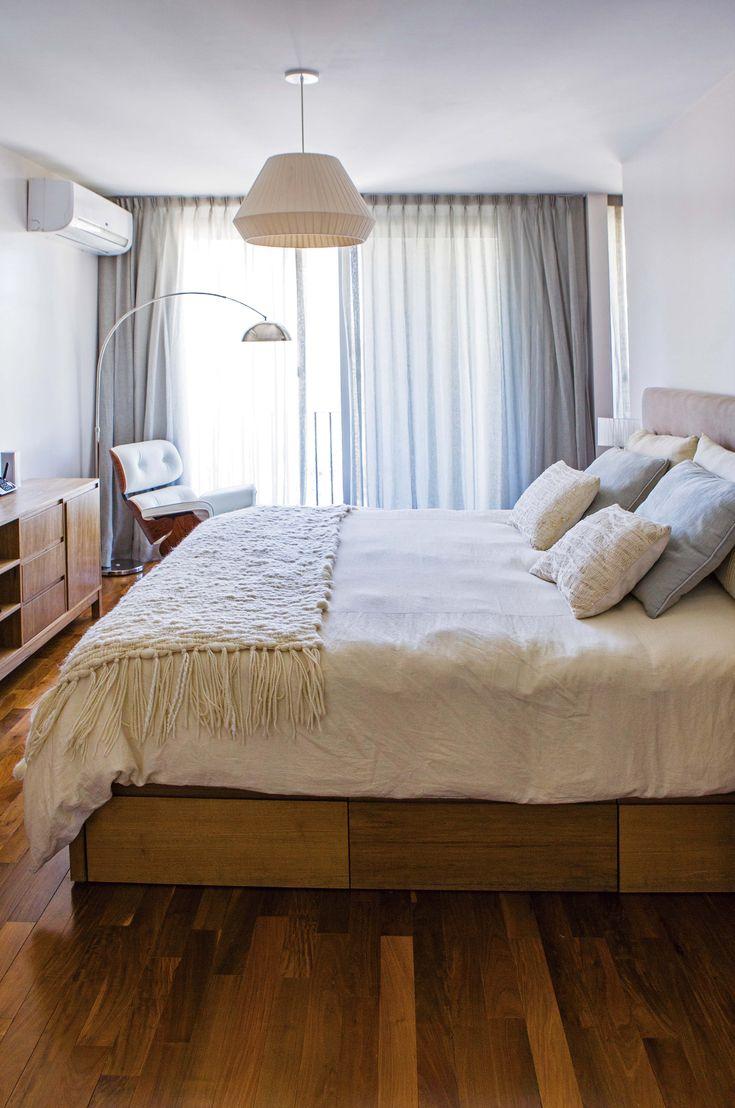 Suite principal en un departamento de Palermo con piso de madera y cama de dos plazas con cajones (Mesopotamia), acolchado blanco y manta en crudo tejida.