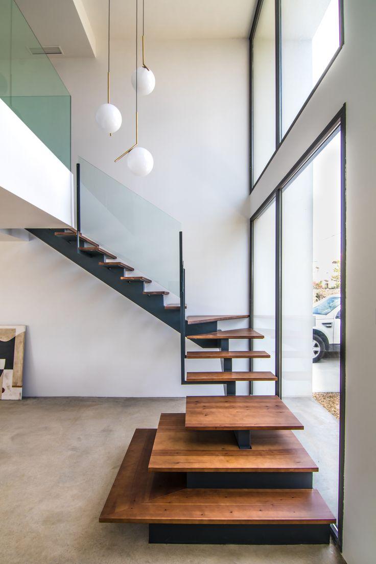 #Escalera de #estructura de #hierro #lacado en gris y con #escalón de arranque, #huellas y #zona de #descanso en #madera #natural #tintada.