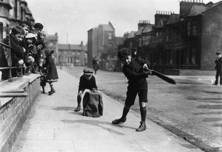 1927: Cockney children play a game of cricket in a London street. (Photo by Central Press/Getty Images)