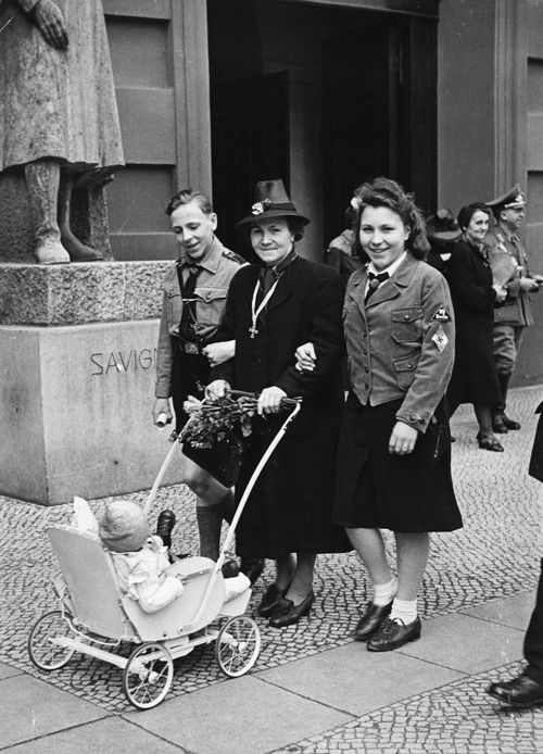 """ORIGINAL CAPTION: """" """"Aryan"""" women who were the mothers of """"child-rich"""" families were given extra food, home help, and holidays. They were even awarded medals. A German mother who has just received the Mother's Cross pushes a baby carriage, accompanied by two of her older children in their Hitler Youth and League of German Girls uniforms. Berlin, Germany, 1942."""""""