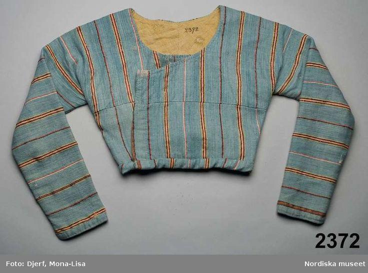 Kvinnotröja s.k. tvärarmatröja, av halvylle med vit linvarp och inslag av entrådigt ullgarn i treskaftad kypert, ljusblå botten med smala ränder i rött, gult, svart, vitt. Skuren på 1700-talsvis med ärmar i ett med bålens 2 stycken med söm i ryggen och i sidorna Skarvad tvärs över båda framstyckena med mönsterpassning. I nederkant påsydd dubbel kant 2,2 cm bred. Vid halsringning, raka framkanter utan knäppning...