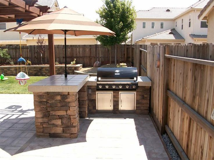 Outdoor entertaining area - love the stone base, built in grill, and umbrella.