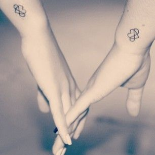Awesome looking wrist tattoos placed on 2 wrists of 2 sisters picturing a heart with infinity symbol. Lovely...