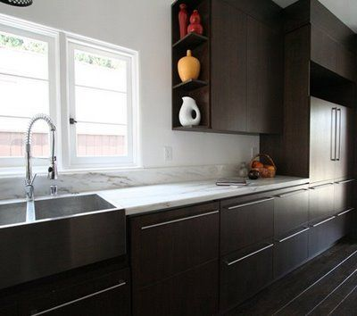 Gourmet kitchen with dark stained wood cabinets and drawers and marble countertop