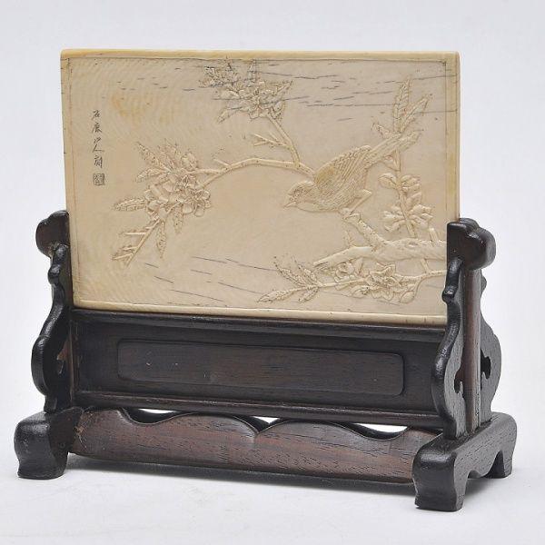 Antiga placa chinesa esculpida em marfim sustentado em base de madeira. Apresenta no anverso paisagem campestre esculpida em alto relevo e, no verso, passarinhos em galhos de árvores esculpidos em relevo. Período imperial. Apresenta escritas tanto no verso como no anverso. Medida da placa de marfim: 9 x 14 cm. Medida base: 9 x 16 cm.