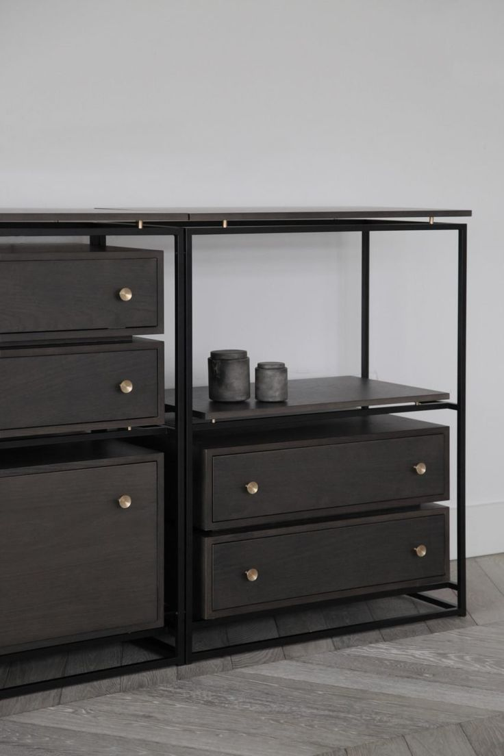 """Shelves can be used as single pieces or placed alongside one another to form longer sections of storage that can double as room dividers. Pieces fit onto brass pegs, so they appear to be """"hovering"""" in the black steel support."""