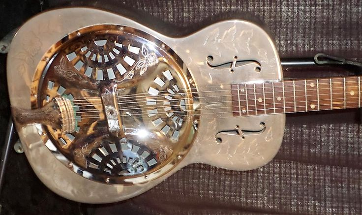 """1973 Dobro Model 36 """"The Rose"""" Resophonic Guitar. Brass body with chrome plating. 14-Fret neck. Rose and ornamental engraving on top and back of body.One of the first years for the OMI models, which are good guitars.Original aluminum cone with biscuit bridge.Fitted with much superior Grover tuner..."""