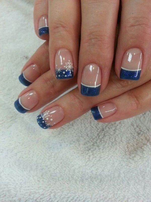 Sensational looking snowflake inspired French manicure. The nails are coated with clear polish as base and tipped with midnight blue coat. Atop the midnight blue French tips are thin snowflake shapes that look like they are slowly falling onto your finger. The French tips are also lined with white nail polish for accent.