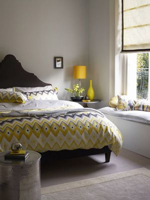 Grey painted bedroom with bright citrus home accessories -walls in dulux clouded pearl