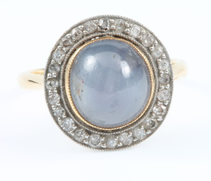 Lot 648, An 18ct yellow gold star sapphire and diamond cluster ring, the centre cabuchon cut stone surrounded by 24 brilliant cut diamonds, size L, sold for £360