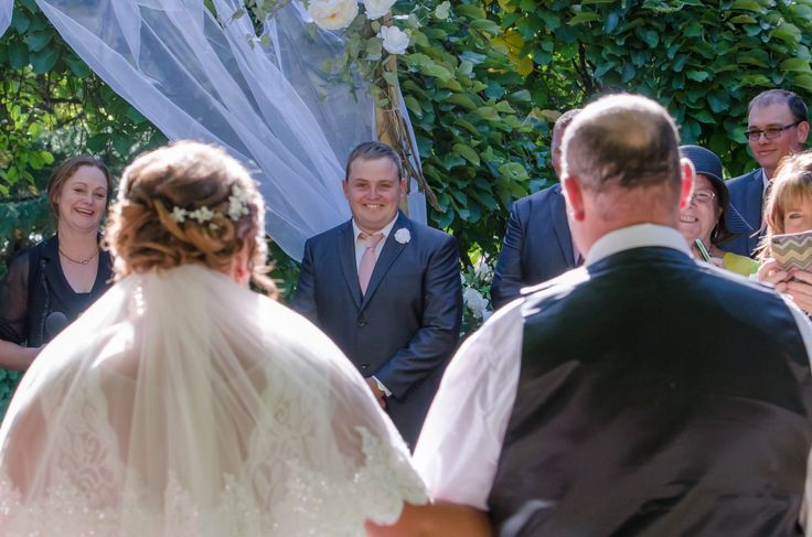Wedding Photographer - Candid Photos of a Lifetime  The grooms 1st look of his bride walking down the aisle toward him.