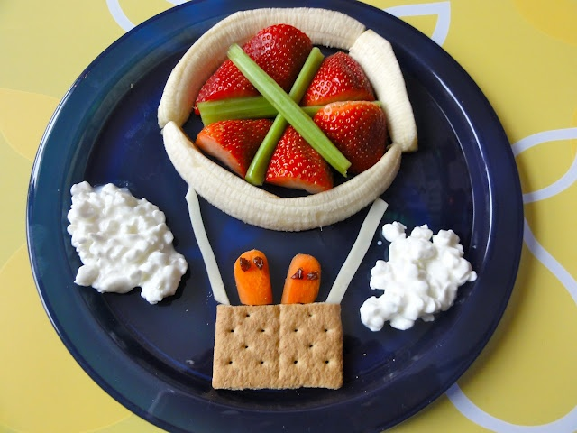 Kid's Fun Eat's ~ Basket is a graham cracker, ropes are string cheese thinly cut, balloon circle is made from a banana cut in half lengthwise and made to look like a circle, interior is strawberries and celery.  The clouds are cottage cheese and the people are carrots with raisins cut into fourths.