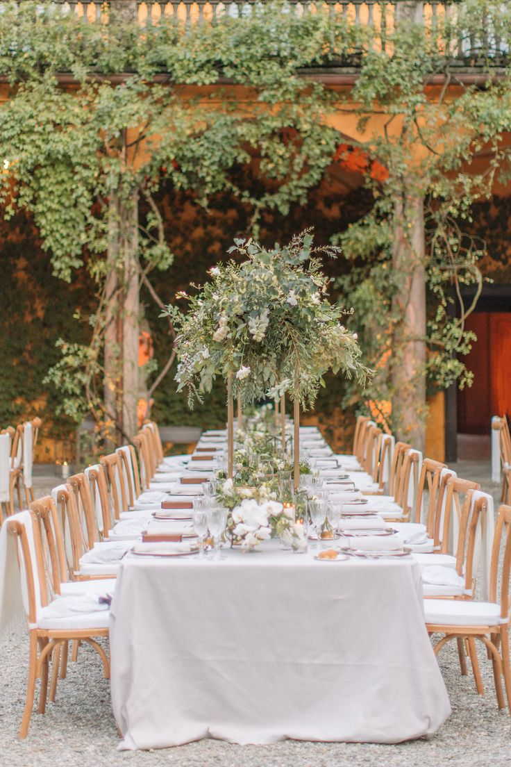 Natural floral decor for the courtyard of this Italian villa. We used wild greenery over head and small compositions along the tables to enhance the natural plants of the villa. by @TheLakeComoWeddingPlanner