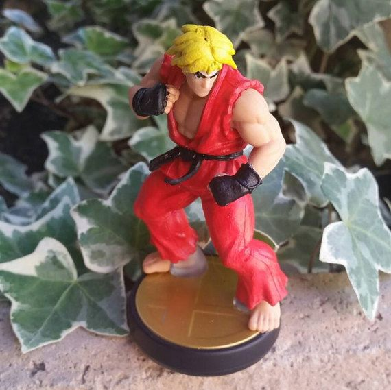 Street Fighter has a multitude of fighters, and the two most popular are Ryu and Ken. The Smash Bros amiibo line finally got Ryu, but what about his counterpart? This custom amiibo takes the Ryu figure and transforms him in to Ken.  Shoryuken!  Hand molded and painted, and varnished for long-lasting display. This street fighter custom toy is made from a Ryu amiibo and will therefore scan in as such for play with Super Smash Bros on the Wii-U and new3DS systems.  Having Ryu on your shelf…