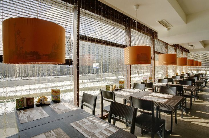 Creative Restaurant Interior Design with Unique Decoration:Orange Pendant Lighting And Dark Dining Chairs With Dining Table In Glass Restaurant Design
