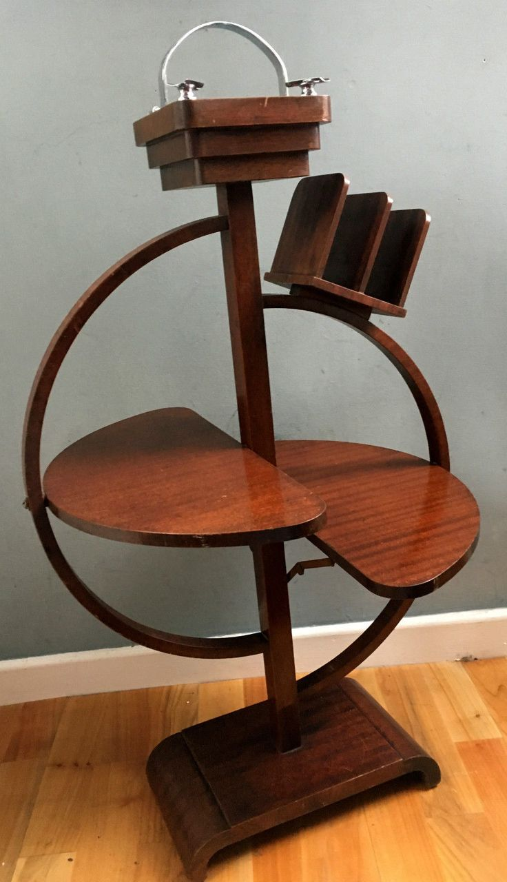 Circular bent wood frame mounted on a curved shoulder base plinth. 2 inner swing tier lock hinged fold away table shelves with a news paper or letter rack mounted to the top of the curved frame. The boxed center support is top mounted with a wood terraced ash tray with an original period glass liner.   eBay!