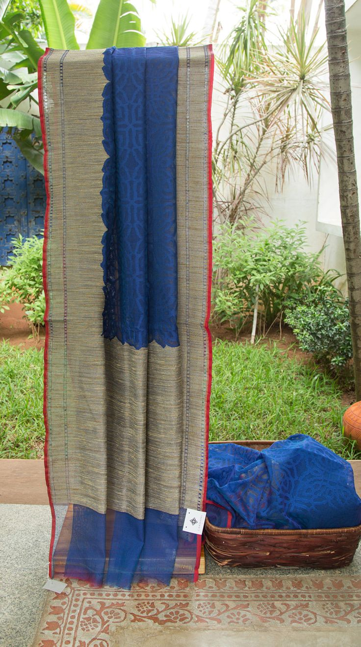 This striking navy blue net sari is handwoven in benares and has an over all abstract pattern in berry blue thread work. The selvedge is in a contrasting berry red while the border and pallu have a…