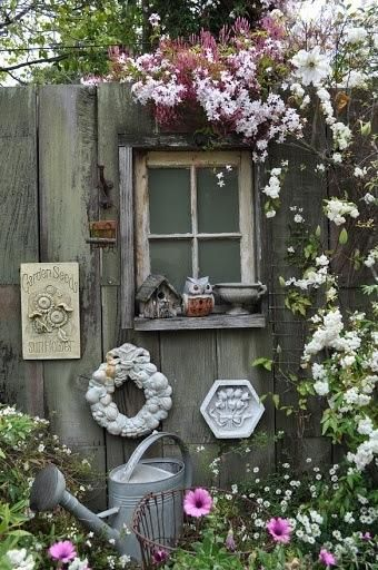 Great way to camouflage the backyard fence - window and climbing plants (minus the wreath).