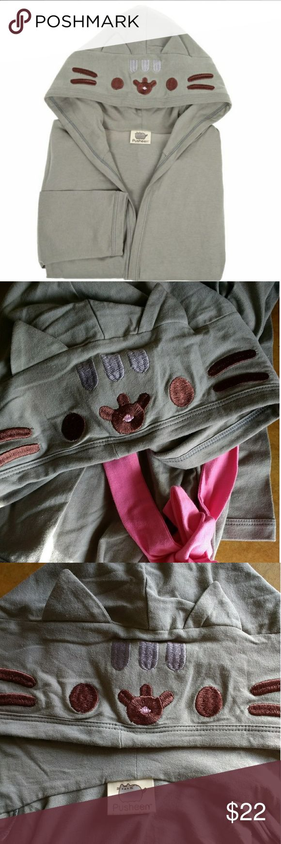 Pusheen the Cat Sleeping Robe 😻 NEW tag fell off Get cozy with this super cute Pusheen the cat robe. Colors Gray and Pink adjustable strap on the waistline. It's 100% Cotton. Sleeping robe for girls size 16. Measurements when laying flat: ~ 30 in length from the hood seam till the bottom. ~ 17 in armpit to armpit (chest) at ease. Of course you can put it on and it doesn't necessarily have to close all the way to be worn. I was very surprised when I was measuring, I tried it on and it fit…