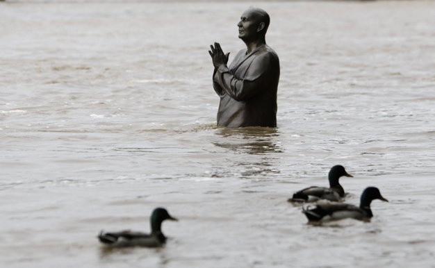 Ducks waddle past the statue of world harmony leader Sri Chinmoy, partially submerged by the water from the rising Vltava river, in Prague (Reuters)